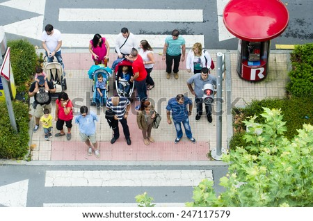 PONTEVEDRA, SPAIN - AUGUST 9PONTEVEDRA, 2014: A group of people waiting at a crosswalk for the light to turn green. - stock photo