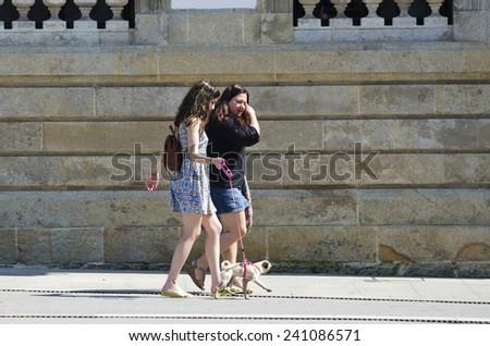 PONTEVEDRA, SPAIN - JULY 25, 2014: Two women walking a dog down the street a sunny summer day. - stock photo