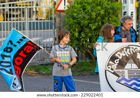 PONTEVEDRA, SPAIN - JUNE 21, 2014:A child waves a flag during a ecological demonstration against the permanence of paper pulp industry in the Ria de Pontevedra. - stock photo