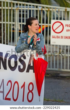 PONTEVEDRA, SPAIN - JUNE 21, 2014: A young woman holds a placard during a ecological demonstration against the permanence of paper pulp industry in the Ria de Pontevedra. - stock photo