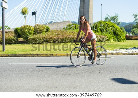 PONTEVEDRA, SPAIN - JUNE 21, 2015: A young woman riding a bicycle on one of the roundabouts of the city .. - stock photo