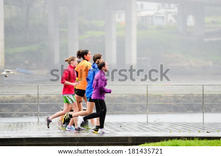 Pontevedra, SPAIN - MARCH 2, 2014: People practice track and field one day of heavy rain, on a track for running and walking in the city of Pontevedra. - stock photo