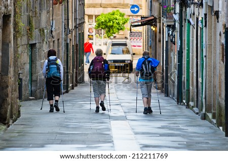PONTEVEDRA, SPAIN - MAY 31, 2014: Some pilgrims loaded with backpacks, walk through the historic center of the city, on the Camino de Santiago. - stock photo