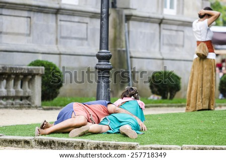 PONTEVEDRA, SPAIN - SEPTEMBER 6, 2014: A couple resting in the grass, dressed in costumes of the Middle Ages, in medieval festival held each year in the historical district of the city. - stock photo