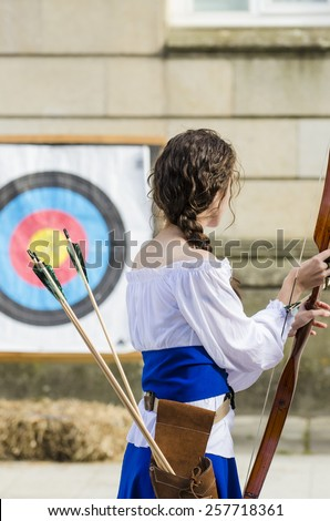 PONTEVEDRA, SPAIN - SEPTEMBER 6, 2014: A woman archer try their aim on a target, dressed in costumes of the Middle Ages, in medieval festival held each year in the historical district of the city. - stock photo