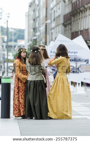 PONTEVEDRA, SPAIN - SEPTEMBER 6, 2014: A young girls chatting, dressed in colorful costumes of the Middle Ages, in medieval festival held each year in the historical district of the city. - stock photo