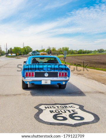 PONTIAC, IL/USA - MAY 5: Classic car and Route 66 shield at historic intersection; Route 66 originally went left but has been rerouted to the right, on May 5, 2013 between Odell and Pontiac, Illinois. - stock photo