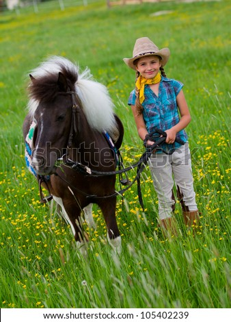 Pony and girl - lovely cowgirl  is grazing little pony on the meadow - stock photo