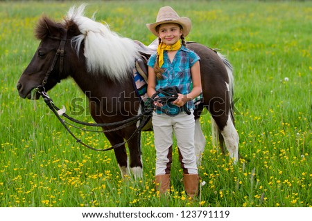 Pony and girl - lovely girl is grazing little pony on the meadow - stock photo