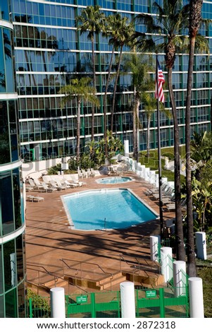 Pool and hot tub in front of the hotel with an American flag. - stock photo