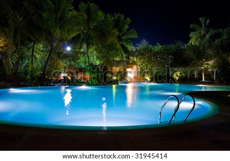 Pool and waterfall at night - vacation background - stock photo