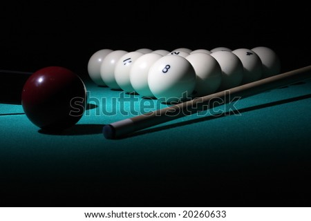 "Pool balls on light beam. Balls pyramid with number 8 ball on a foreground. ""Low-key"" scene. - stock photo"