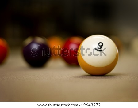 Pool balls on the table with shallow depth of field, focus on the nine ball - stock photo