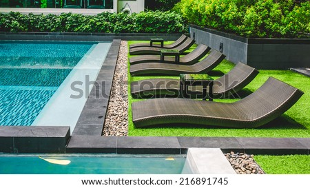 Pool bed beside on the tropical resort swimming pool.  - stock photo