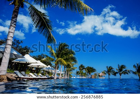 Pool by the sea. Beach, palm trees, resort
