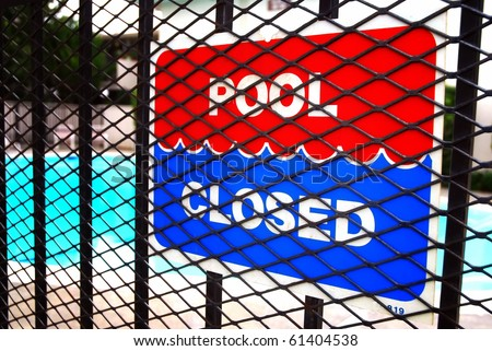 Pool closed sign on fence outside apartment complex swimming pool