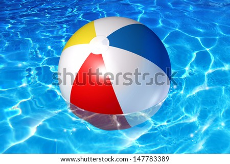 Pool fun concept with an inflatable plastic beach ball floating in cool crystal clear reflective water as a symbol of vacation relaxation in a family backyard or leisure activity at a holiday hotel. - stock photo