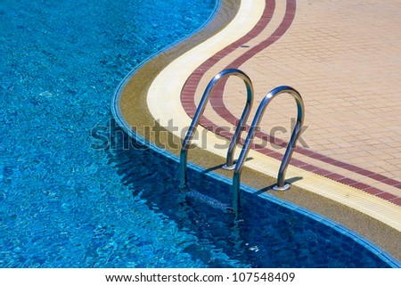 Pool ladder and swimming pool - stock photo