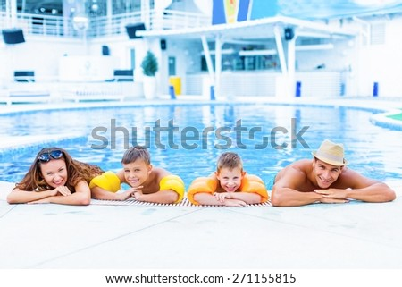 Pool. Mother with three children having fun in the pool, swimming in blue transparent water, active cheerful family spending summer holidays together - stock photo