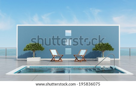 Pool on waterfront with two deckchair and plants in front a blue wall