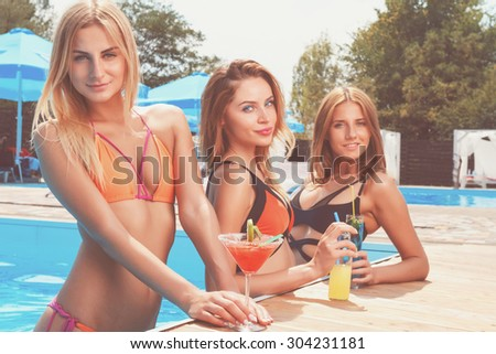 Pool party. Three pretty young girlfriends standing in pool and holding cocktails. - stock photo
