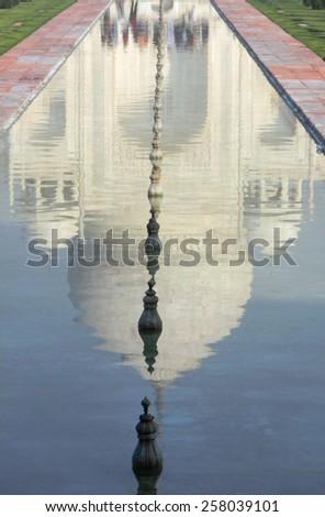Pool reflection of the iconic Taj Mahal mausoleum in Agra, India - stock photo