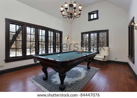 Pool room in suburban home with wall of windows