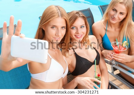 Pool selfie. Group of attractive young women lying on chaise longue with cocktails and doing selfie. - stock photo