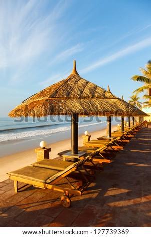 pool, sunbed, umbrellas on background of the sea and sky at dawn - stock photo