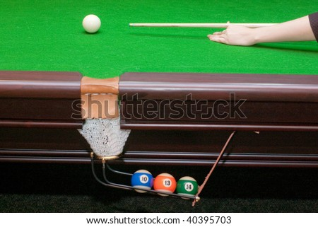 Pool table with filled pocket and hand ready to hit with billiard cue white ball, selective focus