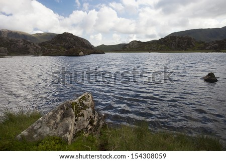 pool up a mountain with rock in foreground and mountains in background, haystacks, cumbria - stock photo