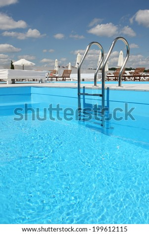 pool with a ladder with beach loungers in the background - stock photo