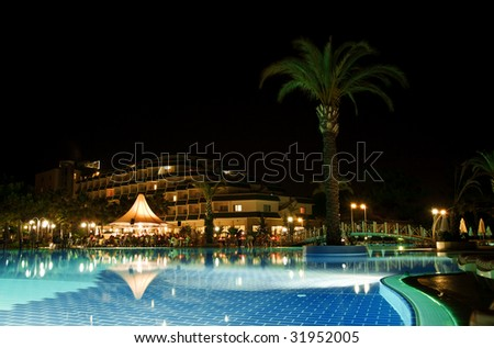 pool with blue water is lighted nightly lanterns, pool bar and palm - stock photo