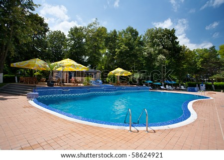 Pool with clear blue water and trees in a summer day - stock photo