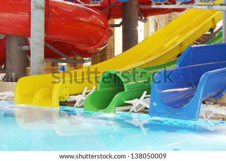 Pool with clear water and multi-colored water slides in indoor aquapark. - stock photo