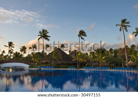 Pool with white bridge and palms on blue sky in the moning
