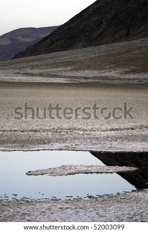 Pools of water in Badwater Basin in Death Valley reflect the surrounding mountains - stock photo