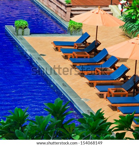 Poolside loungers at an exotic asian hotel. - stock photo