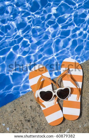 Poolside shoes and sunglasses - stock photo