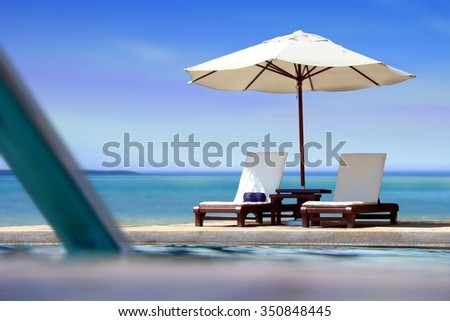 Poolside view near the beach with blue sky - stock photo