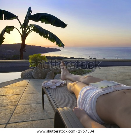Poolside view of the sun setting over the ocean in Costa Rica - stock photo