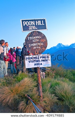 POON HILL, NEPAL - OCTOBER 12, 2008: Poon hill altitude sign, Nepal. Tourists meet the sunrise at top of Poon Hill in Himalayas