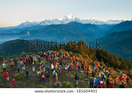 POON HILL, NEPAL - OCTOBER 05, 2012 - Tourists meet the sunrise at top of Poon Hill in Himalayas - stock photo