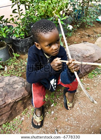 Poor African child playing with some improvised toys - stock photo