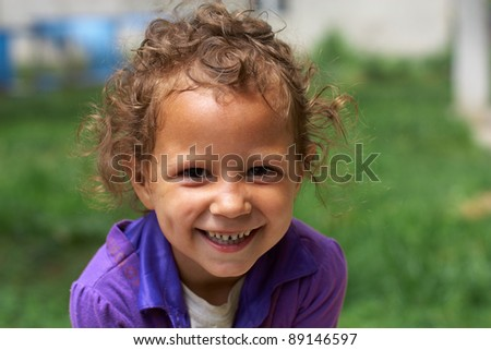 poor and dirty, but still happy and smiling cute little gypsy girl - stock photo