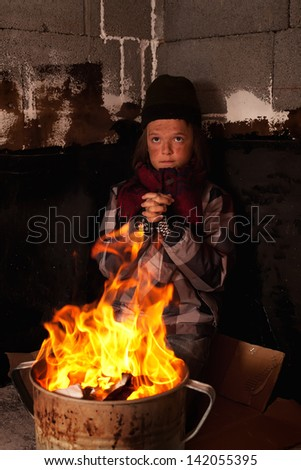 Poor beggar child warming up at the fire made in tin pot - praying thankfully - stock photo