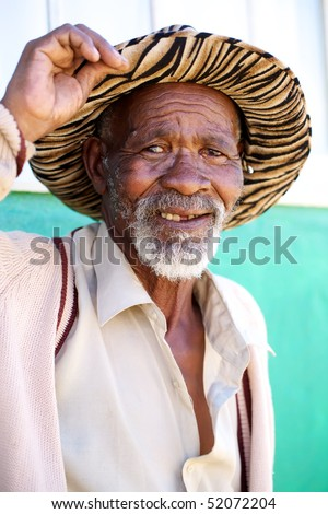 Poor black South African man holding his hat with a friendly expression on his face. - stock photo