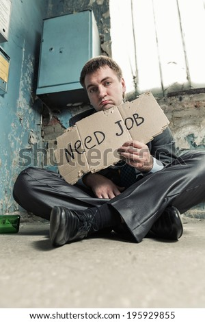 Poor businessman holding sign asking for job - stock photo