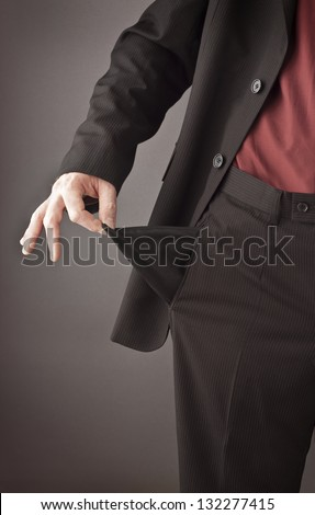 Poor businessman turning his empty pocket inside out to show his broke and out of money. Recession or financial crisis concept. - stock photo