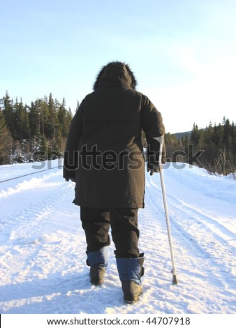 Poor fat disabled woman with a crutch walking on a snowy road - stock photo